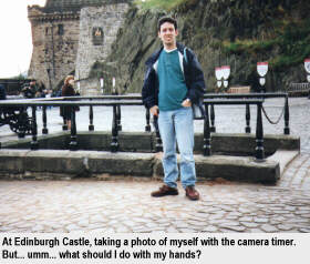 At Edinburgh Castle, taking a photo of myself with the camera timer. But... umm... what should I do with my hands?